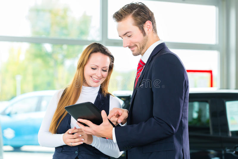 Dealer, female client and auto in car dealership. Seller or car salesman and female client or customer in car dealership presenting the interior decoration of stock photo
