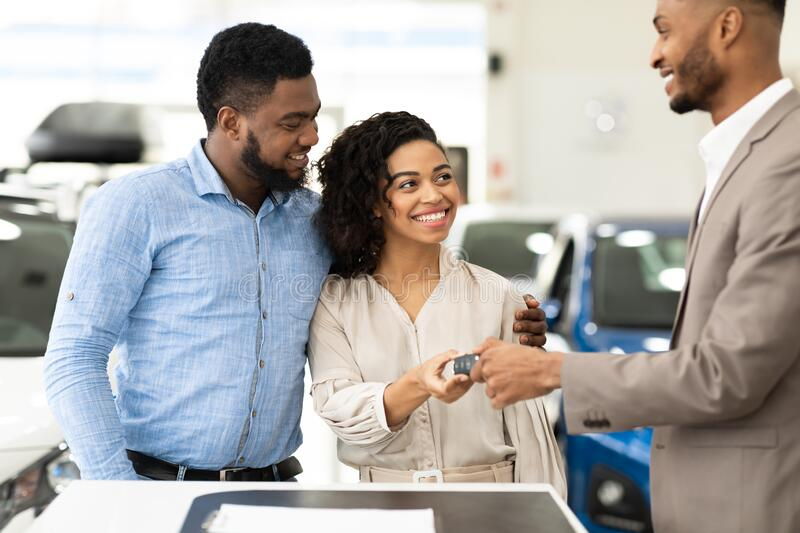 Dealer Giving New Car Key To Buyers Standing In Store. Dealer Giving New Car Key To Joyful Black Buyers Couple Standing In Auto Dealership Store. Family Buying royalty free stock photography