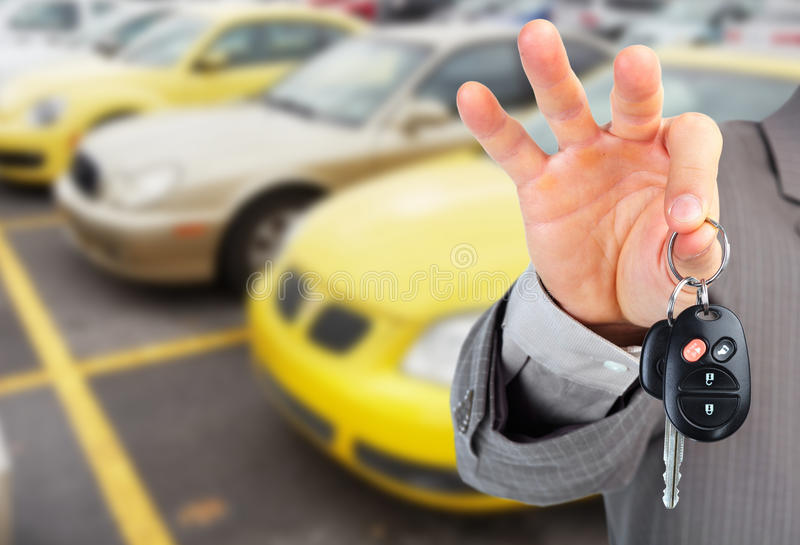 Dealer hand with a car key. Car dealer hand with key. Auto dealership and rental concept background royalty free stock photography