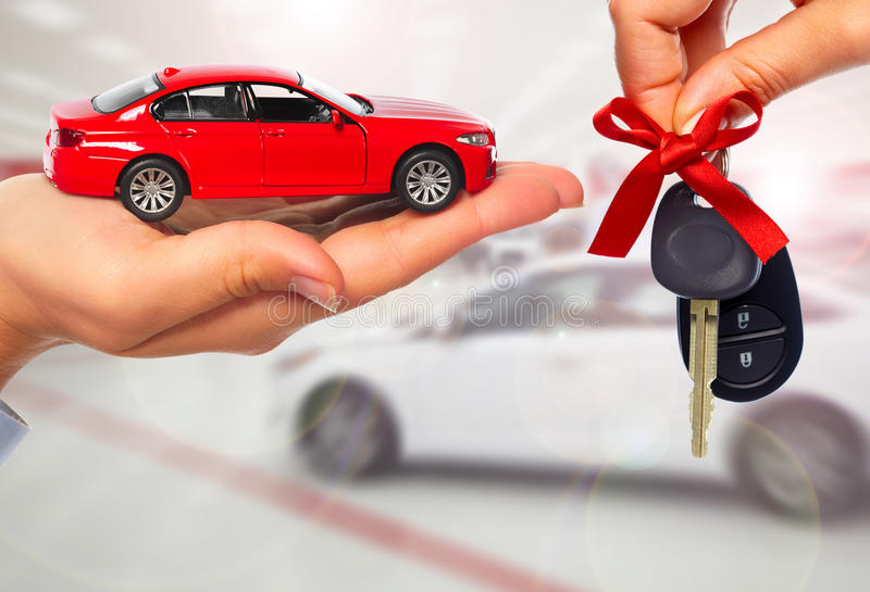 Dealer hand with a car key. Car dealer hand with key. Auto dealership and rental concept background stock photography