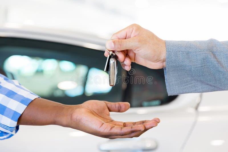 Dealer handing car key. Close up of car dealer handing over new car key to customer at showroom royalty free stock photos