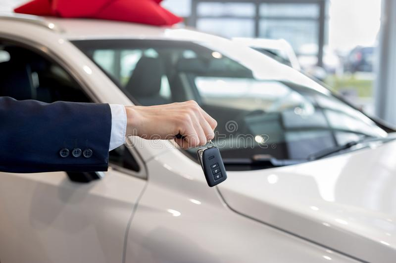 Dealer holding keys to a new car. Modern and prestigious vehicles. stock photo