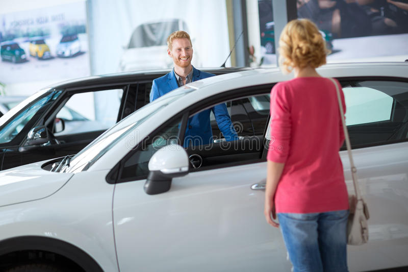 Dealer showing a new car female costumer royalty free stock photos
