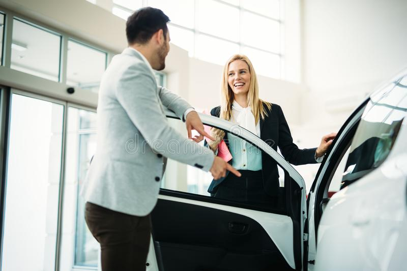 Dealer showing a new car model to the potential customer royalty free stock photography