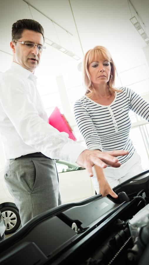 Dealer showing a new car model to the potential customer royalty free stock images