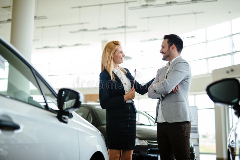 Dealer showing a new car model to the potential customer stock photos
