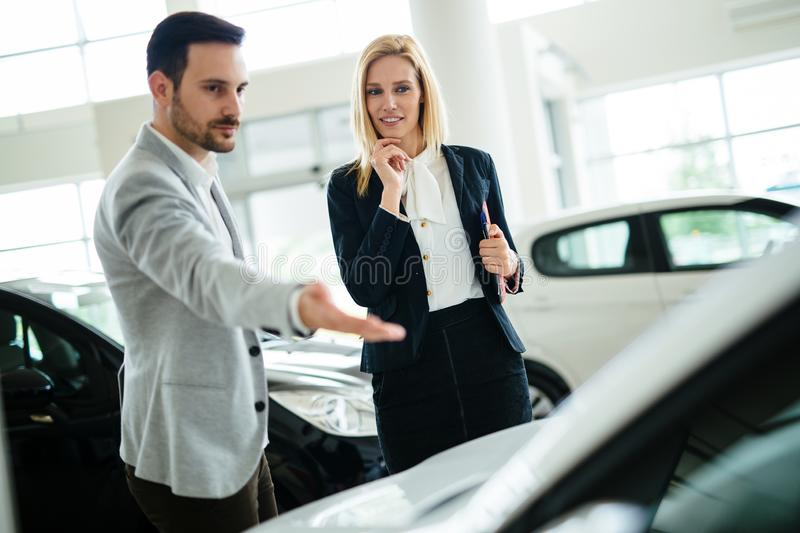 Dealer showing a new car model to the potential customer royalty free stock photos