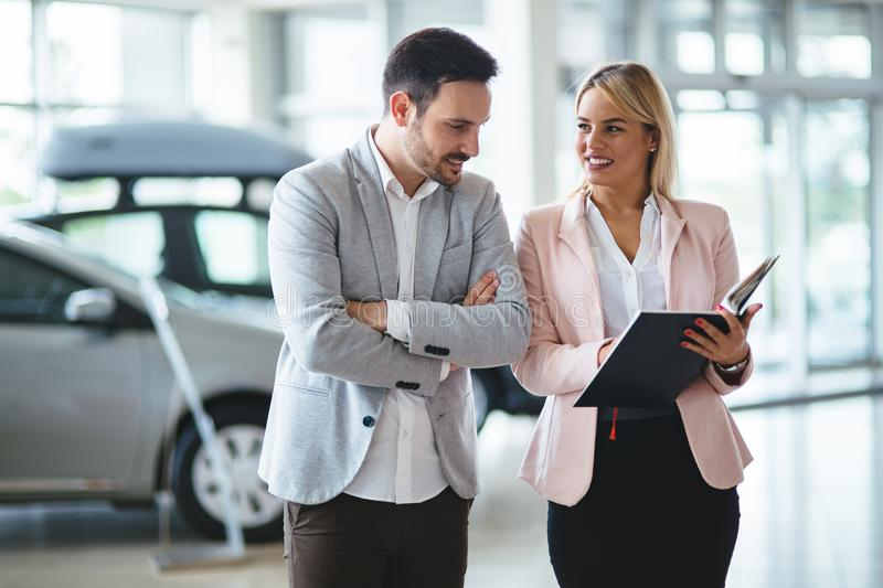 Dealer showing a new car model to the potential customer stock photo