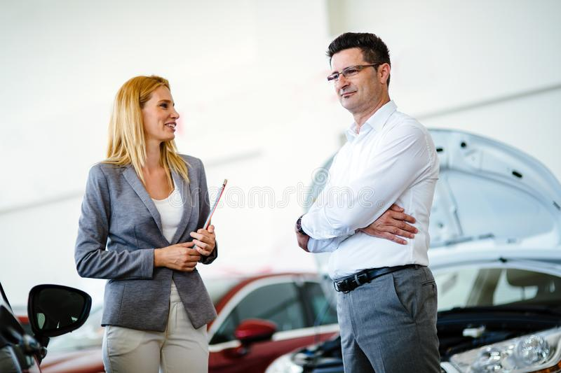 Dealer showing a new car model to the potential customer stock image