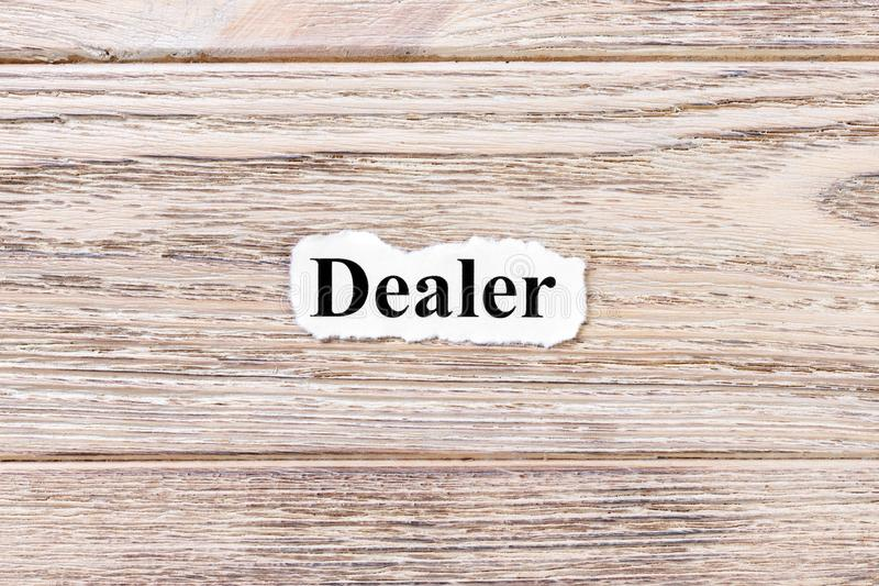 DEALER of the word on paper. concept. Words of DEALER on a wooden background.  royalty free stock image