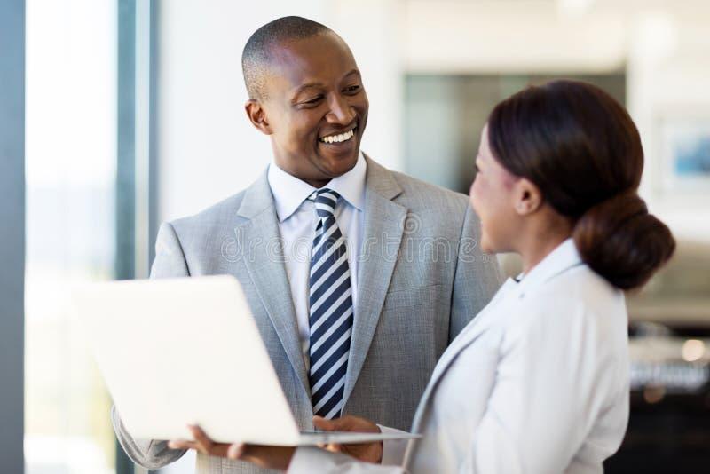 Dealership principal saleswoman. Friendly african vehicle dealership principal and saleswoman working on laptop royalty free stock photos