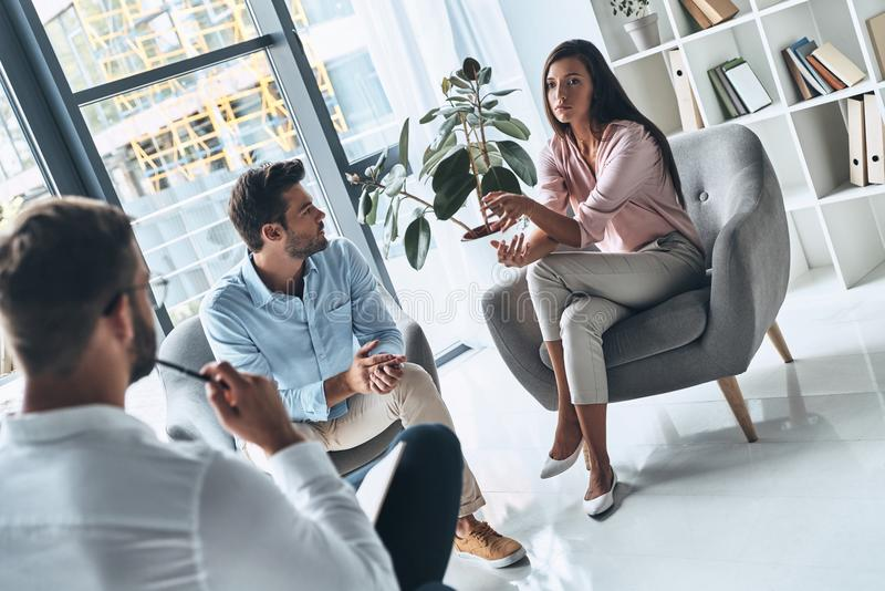 Dealing with betrayal. Young married couple talking while sitting on the therapy session with psychologist royalty free stock photos