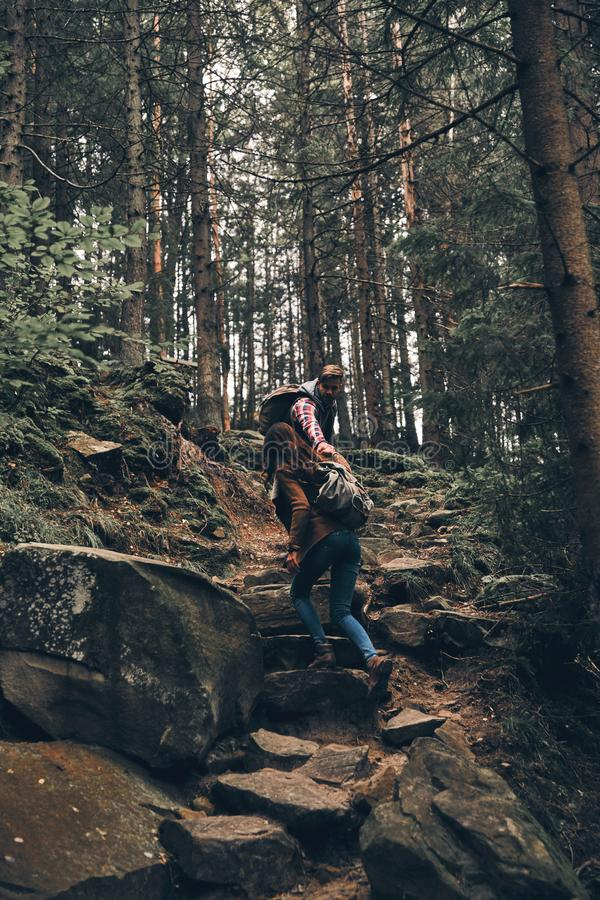 Dealing with difficulties. Full length of young couple holding h. Ands and moving up while hiking together in the woods royalty free stock photography