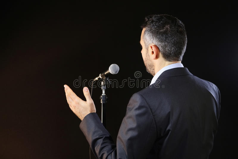 Dealing with the fear of public speaking. Public speaker speaking at the microphone, pointing, in the spotlights, symbol of leadership and international stock photography