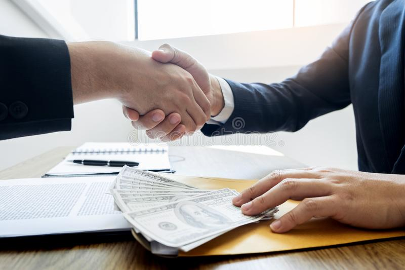 Dealing greeting and partnership meeting concept, businessmen handshaking after finishing up deal contract for both companies stock images