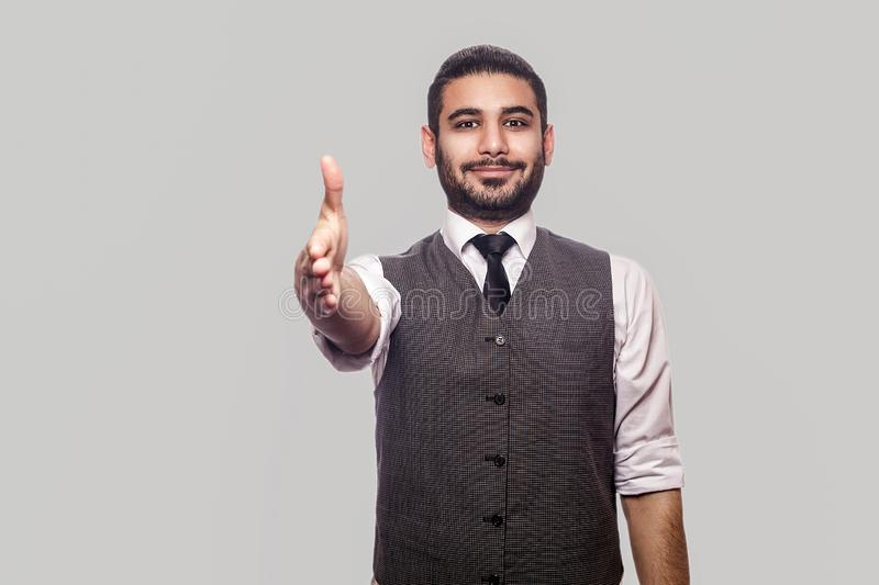 Dealing, handshake and greeting. Portrait of happy handsome bearded brunette man in white shirt and waistcoat standing looking and stock photos