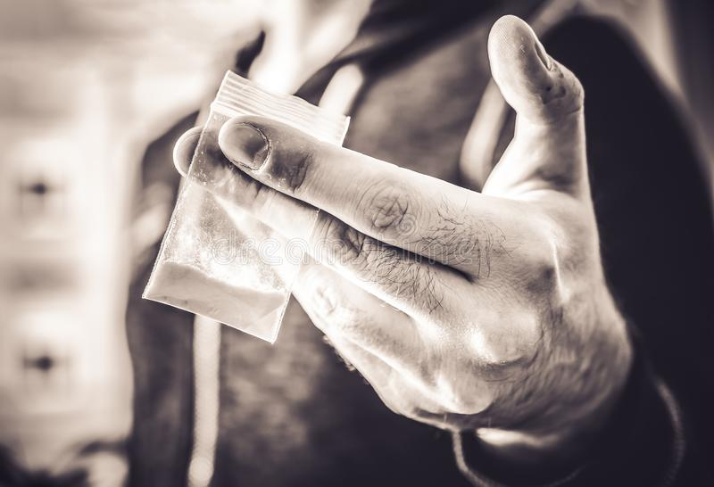 Dealing Illegal Drugs By A Man Holding A Little Bag With White Powder In His Hand In Monochrome Colors. Dealing Illegal Drugs By A Man Holding A Little Bag With royalty free stock image