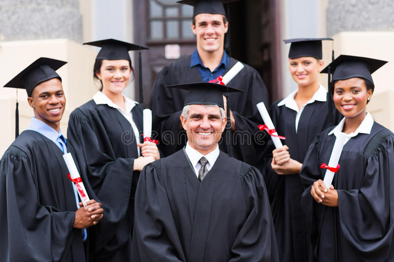 Dean group graduates. Dean standing with group of happy graduates outside university royalty free stock images