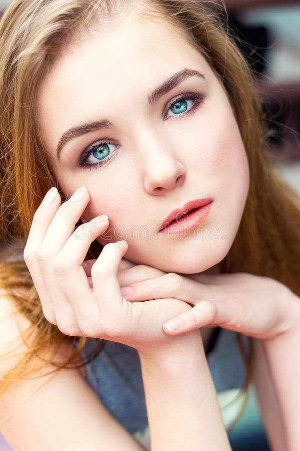 Dear beautiful elegant young girl with blue eyes with regime hair seated. At the table stock images