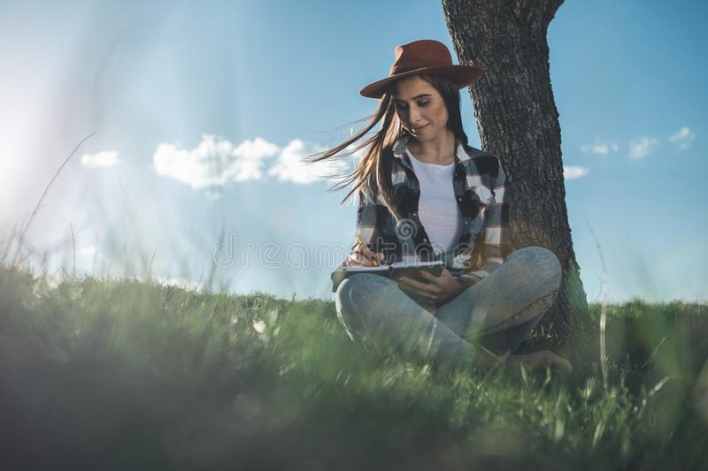 Beautiful girl with pen and notebook on fresh air royalty free stock photo