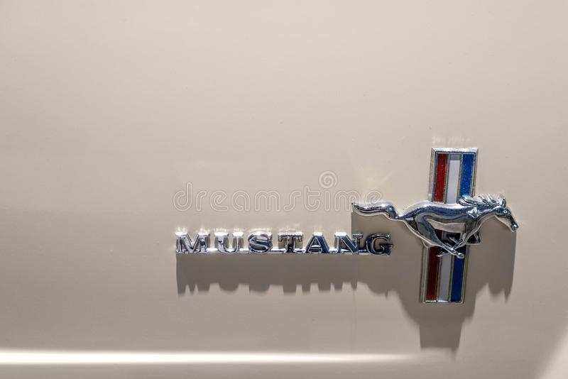 Dearborn, MI / USA - 04.21.2018 : Close-up logo on side of an white Ford Mustang oldtimer. Dearborn, MI USA - 04.21.2018 : Close-up of Mustang logo on side of an stock image