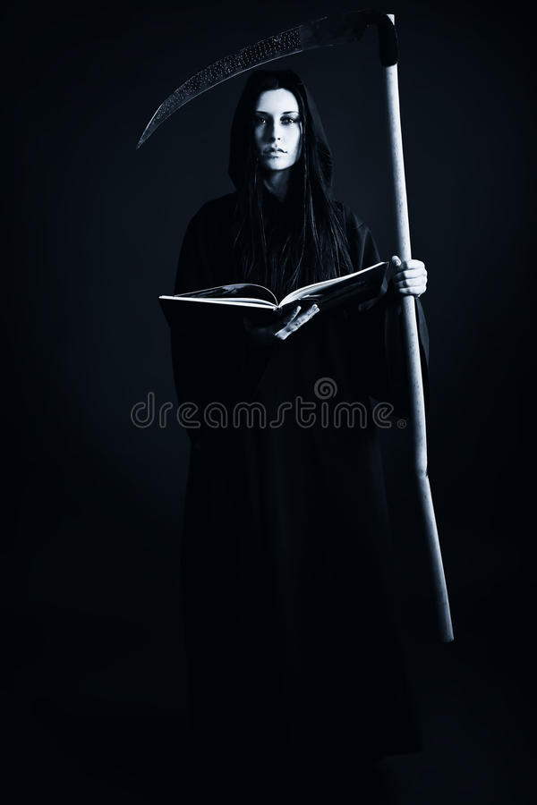 Death. Woman death reaper over black background. Halloween stock photo