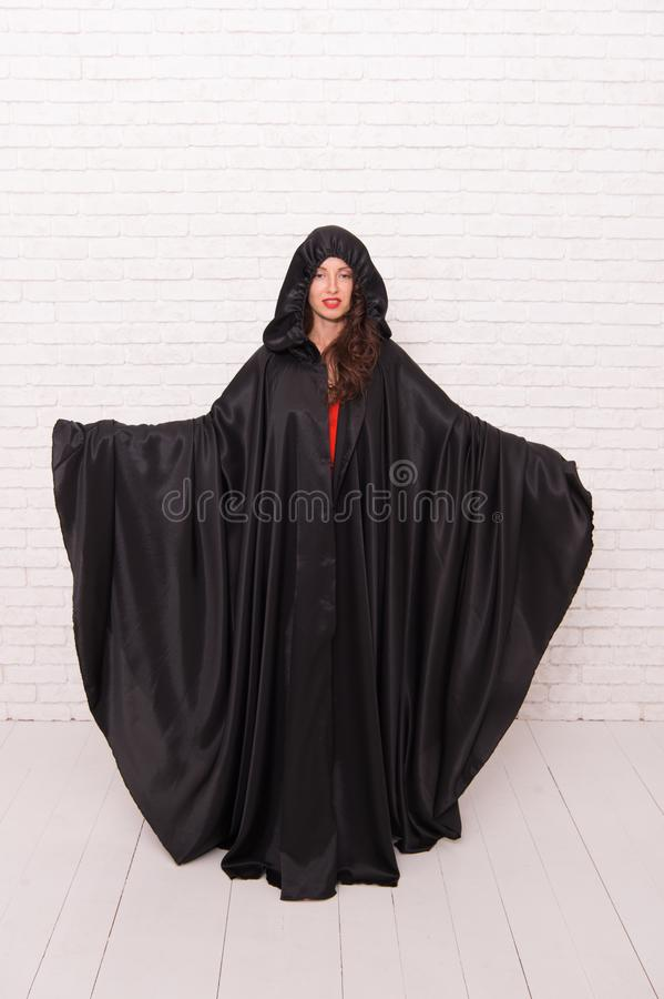 Death in black cloak symbol. Vampire in cloak sexy devil girl. Woman tempting vampire demon. Girl covered with cloak. Devil concept. Halloween masquerade stock photography