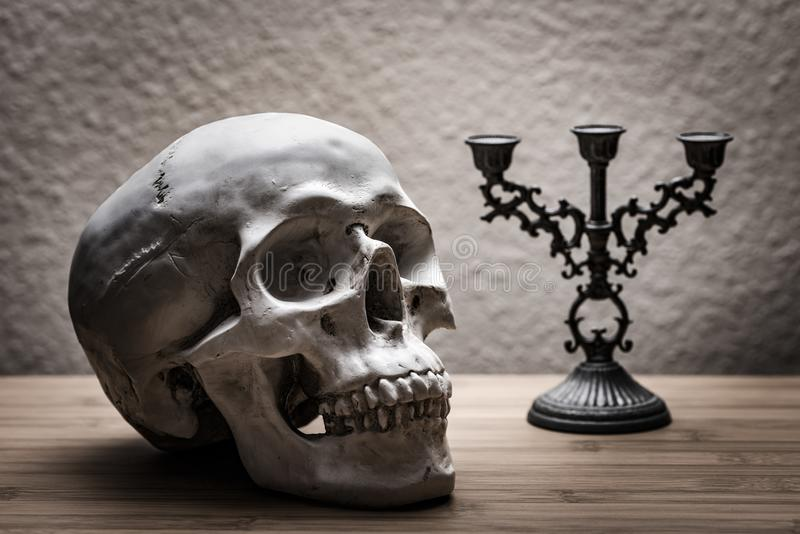 A death`s head with candlestick on a wooden table stock photo