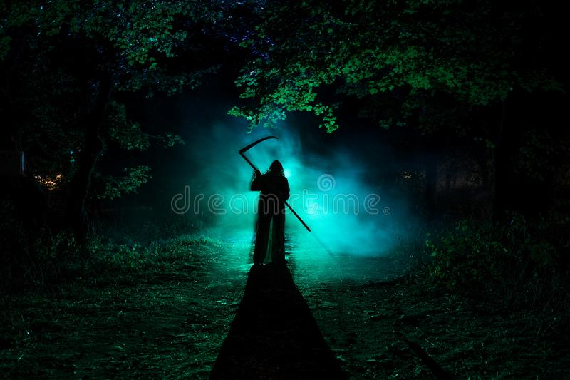 Death with a scythe in the dark misty forest. Woman horror ghost holding reaper in forest stock photo
