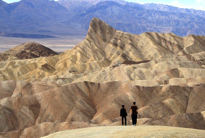 DEATH VALLEY KALIFORNIEN - NOVEMBER 28 2009: Två personer på Zabriskie punkt i den Death Valley nationalparken Kalifornien royaltyfri bild