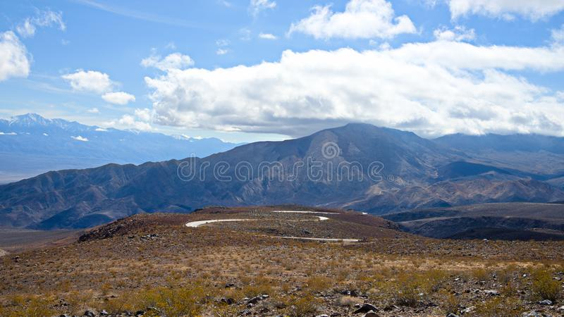 Death Valley National Park clouds and winding road. Death Valley National Park clouds and winding. Death valley national park landscapes. clouds, rocks royalty free stock photography