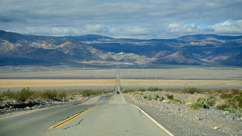 Death Valley National Park - Desolate road. Death Valley National Park borax mule. Death Valley National Park clouds and winding. Death valley national park royalty free stock photography