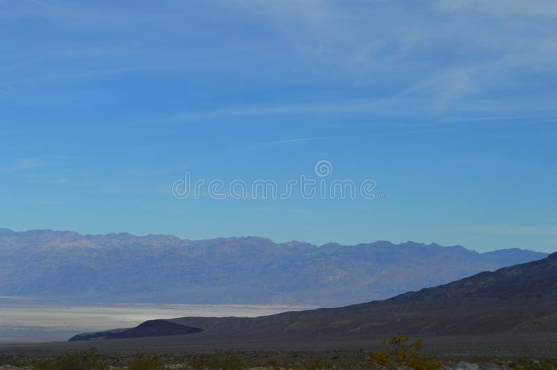 Death Valley Vista from entry point. Sloping hill foreground, mountain range and flloor in distance. Blue Sky, purple mountains stock photo