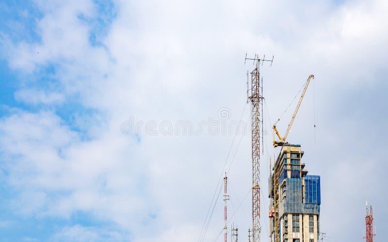 Debajo del edificio alto de la construcción con la grúa de construcción amarilla contra la nube y el cielo azul imagen de archivo