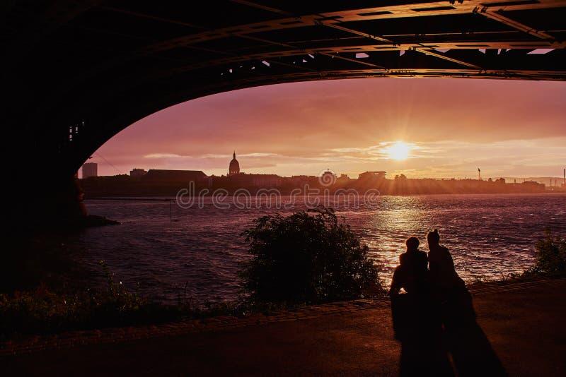 Debajo del puente de Theodor Heuss en la puesta del sol con un par fotos de archivo