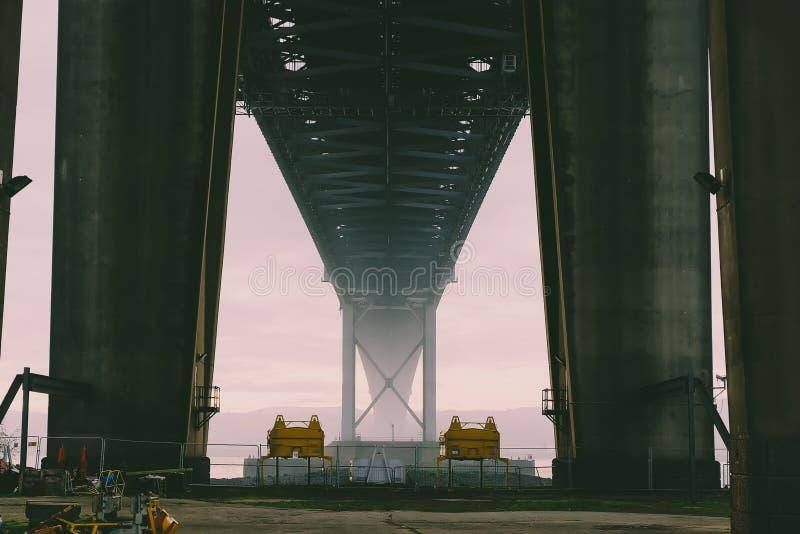 Debajo del puente tirado del puente en distancia con niebla fotos de archivo