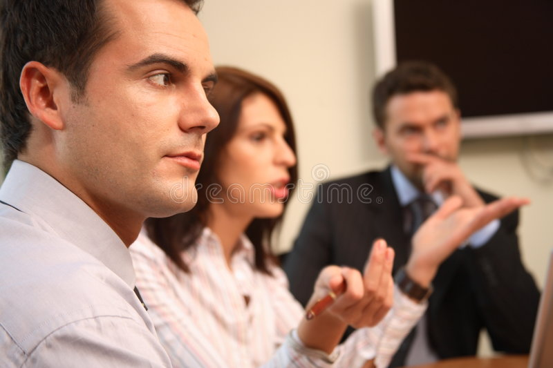 At the debate. Group of business people sitting at the table, working on project -2 men and 1 woman,close up, man and woman blured stock image
