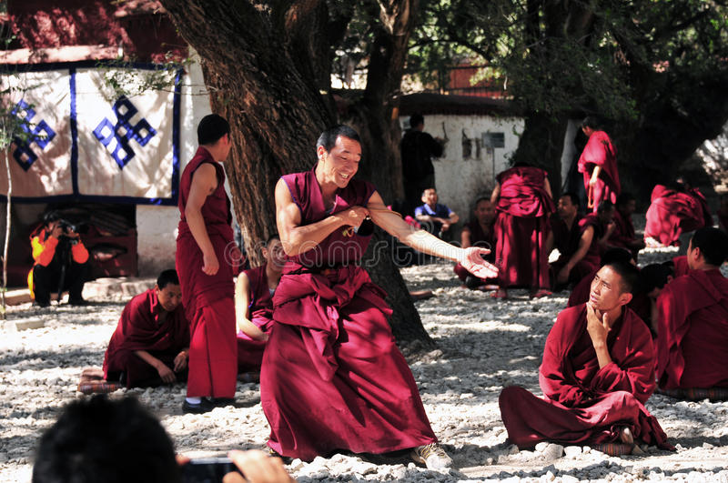 Debating monks in Tibet. Tibetan monks at Sera monastery debating in the courtyard stock images