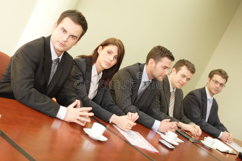 Debating people. Business professionals consisting of one woman and four men, sitting at a conference room table stock image