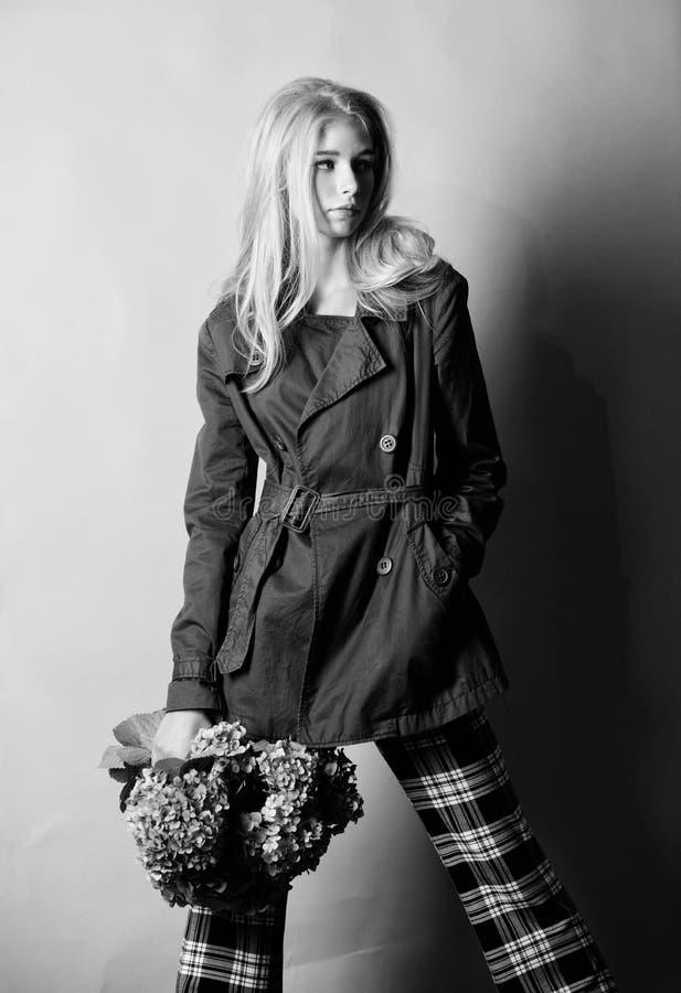 Debe tener concepto Capa de moda Pelo rubio de la mujer que presenta la capa con el ramo de las flores Ropa y accesorio Chica imagen de archivo libre de regalías