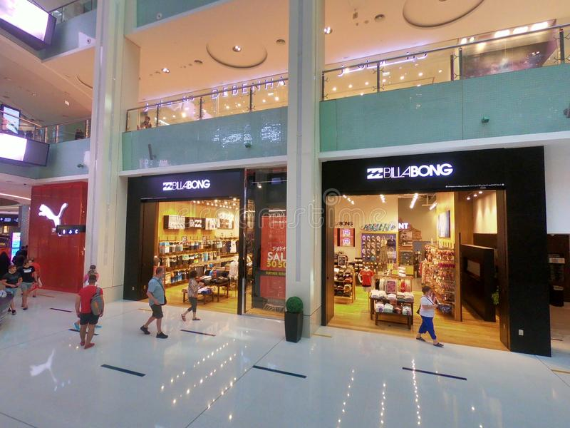 Debenhams, Billabong och kuguar shoppar på den Dubai gallerian - den inre sikten av den största shoppinggallerian för världar arkivfoto