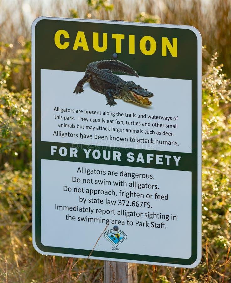 Debido a la presencia de caimanes, una señal de advertencia en el Parque Estatal Big Lagoon foto de archivo