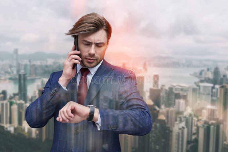 Debo estar allí a tiempo Hombre de negocios preocupante que habla por el teléfono y que mira su reloj mientras que se opone a de fotografía de archivo