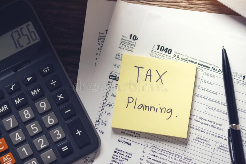 Debt collection and tax planning with deadline calendar reminder note, U.S. tax form 1040, calculator on wooden background. Top. View, Time to payment concepts royalty free stock images