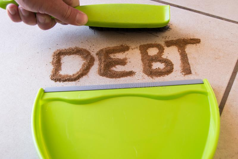 Debt Concept. With debt written in dirt on a floor and a person is about to sweep the debt dirt in a dust pan using a small hand broom stock photography