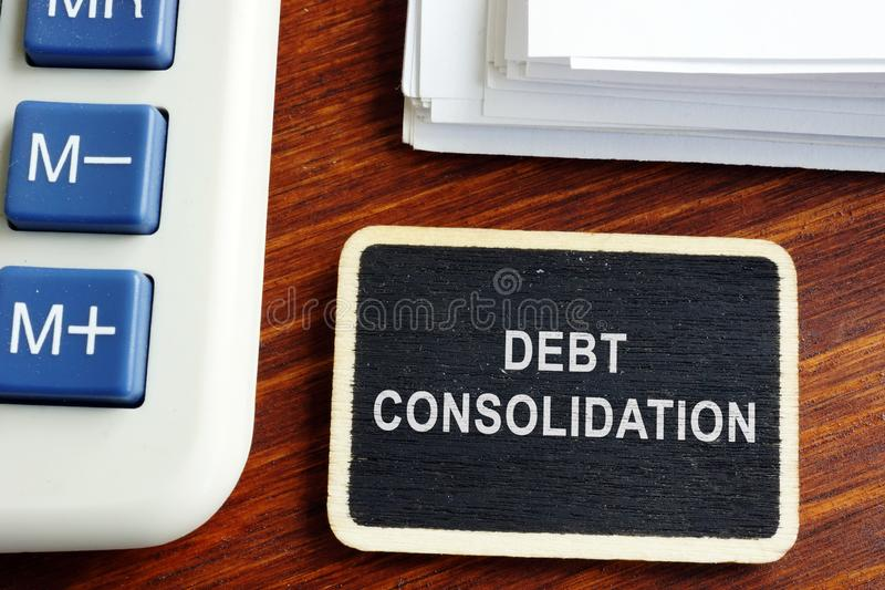 Debt consolidation loan. Nameplate with stack of documents royalty free stock photo
