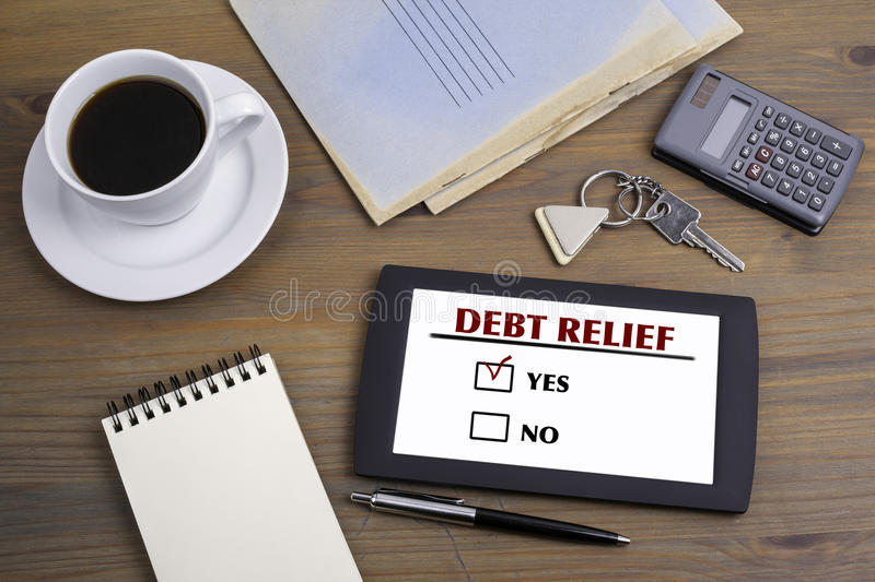 Debt Relief. Text on tablet device on a wooden table.  royalty free stock photography