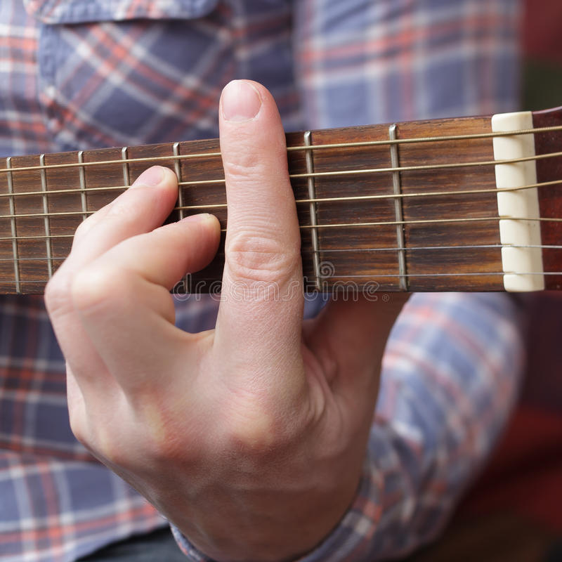 Debugging musical instruments. Young musician sets up a small guitar royalty free stock photos