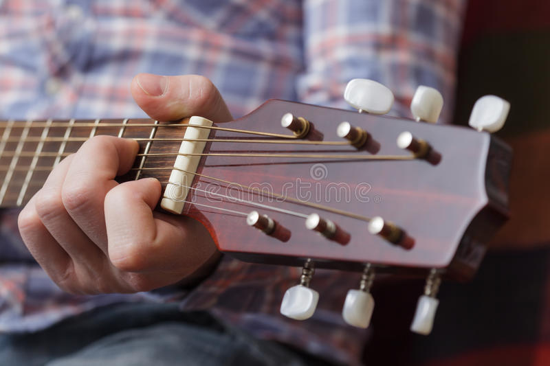 Debugging musical instruments. Young musician sets up a small guitar royalty free stock photo