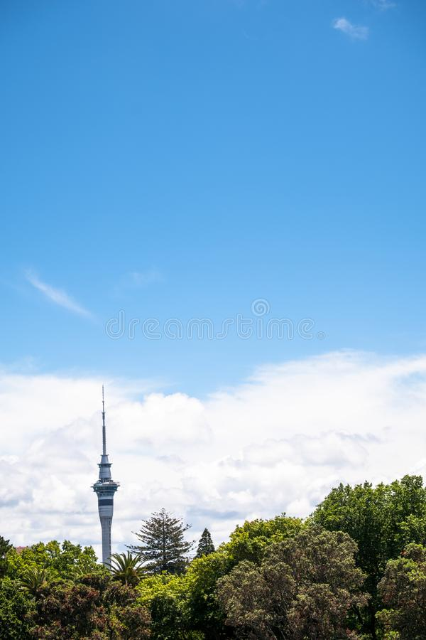 2017, DEC 4 - Auckland, New Zealand - Skytower over the green trees with clouds and blue sky. I. 2017, DEC 4 - Auckland, New Zealand - Skytower over the green royalty free stock photos